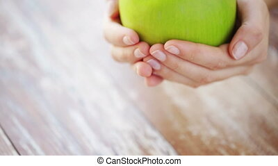 close up of young woman hands showing green apple - healthy...