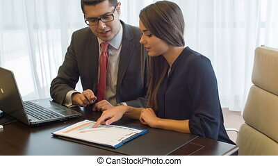 Young dark-haired smiling woman sitting talking with her agreeable boss
