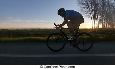 cyclist silhoutte rides bike - healthy man riding bike...