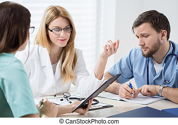 Planning the treatment - Three young experienced doctors...