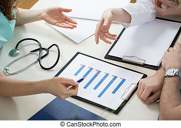 Close-up of test results - Close-up of three physicians...