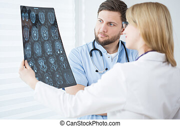 Brain scanning - Two young doctors looking at patient's...