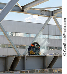 welder welds the steel bridge construction - worker welder...