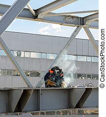 welder welds the steel bridge construction - worker welder...