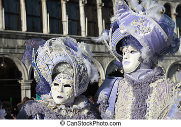 masked persons in ornate medieval costume on San Marco...