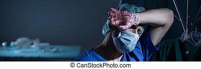Surgeon being tired after operation - Image of surgeon being...