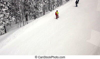 Snowboarders and skiers ride on the slope view from the lift