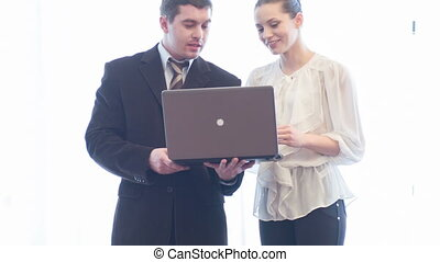 Two smiling assistant-workers standing together with notebook