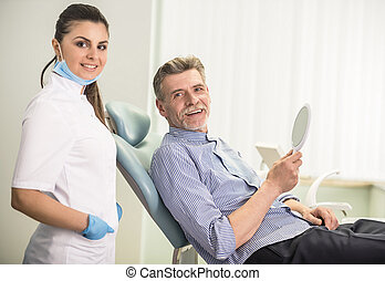Senior male - Female dentist with his senior client in...