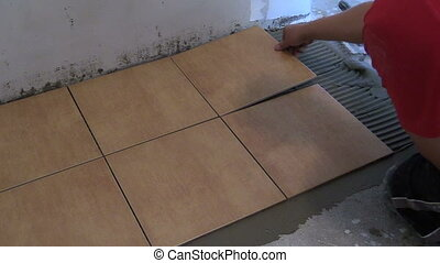 handyman lay tile - Handyman lay floor tiles at home Closeup...