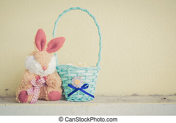 rabbit doll and blue basket on old yellow background