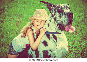 my dog - Happy little girl with her mastiff dog on a meadow...