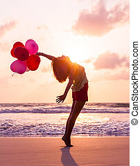 Beautiful girl with colorful balloons on sea shore