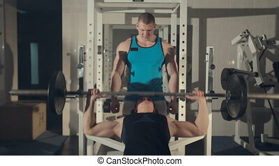 Man training with personal trainer at the gym, pumping iron