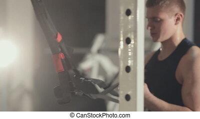 Man trains biceps in gym