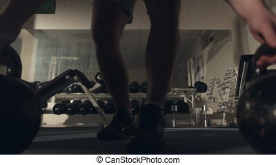 Sweaty man pushed from floor with dumbbells in the gym -...