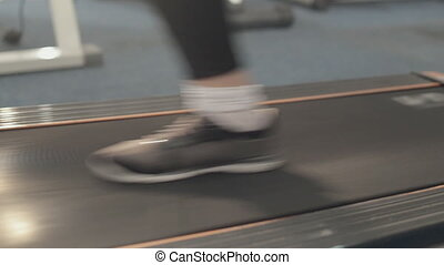Close-up of a girl walking on a treadmill