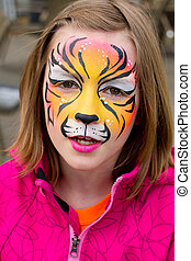 Pretty girl with her face painted as a tiger