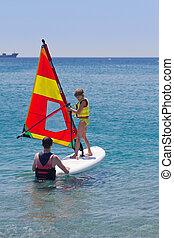 Beginner windsurfer girl taking lessons - Little girl taking...
