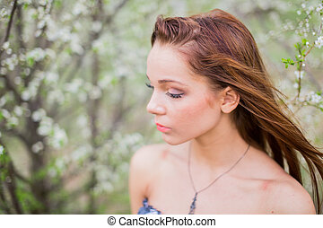 Young lady in spring orchard - Portrait of a red-haired...