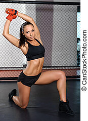 Female kickboxer poses at a ring - Fit body Young beautiful...