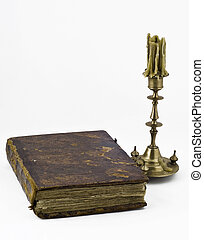 Candlestick and a book - An old candlestick with antique...