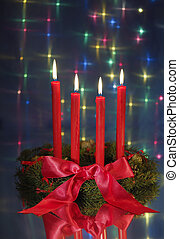 red candles on christmas wreath against blue glow background...
