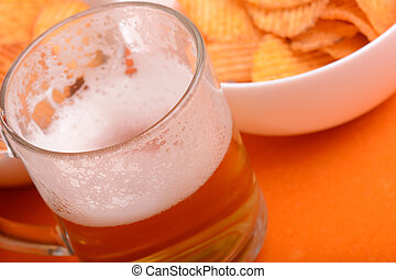 Glass of light beer and potato chips on a wooden table