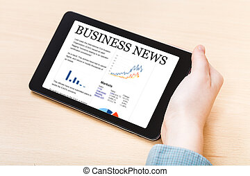 businessman hand hold tablet PC with business news