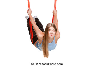 Young woman doing anti-gravity aerial yoga in red hammock on...