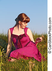 Beautiful girl in pink dress sitting on grass