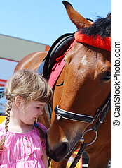Little beautiful girl in pink dress stands near horse