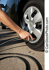 airing up a car tire - A man aring up a car tire
