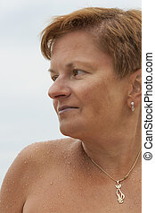 smiling middle aged caucasian tanned naked woman outdoor...