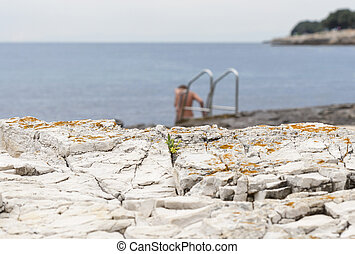 Naked woman bathing in the sea rocky beach with ladder