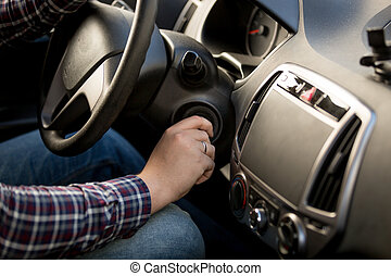 Closeup of man inserting key in car ignition lock - Closeup...
