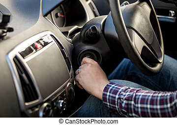 driver turning ignition key in right-hand drive car - Male...