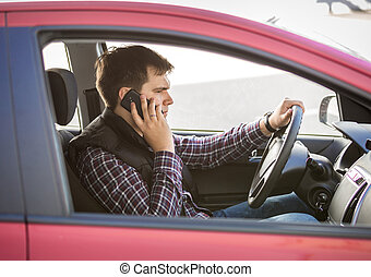 young man talking by phone while driving a car - Portrait of...