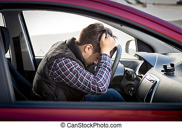stressed man sitting on car drivers seat - Portrait of...