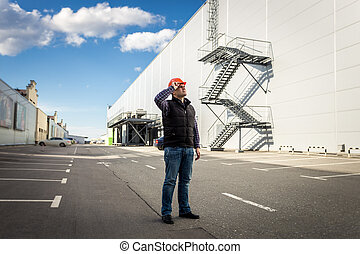 male worker posing on parking of industrial building - Full...