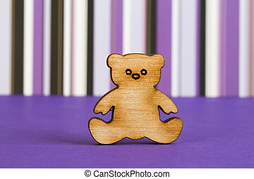 Wooden icon of Teddy bear on purple striped background