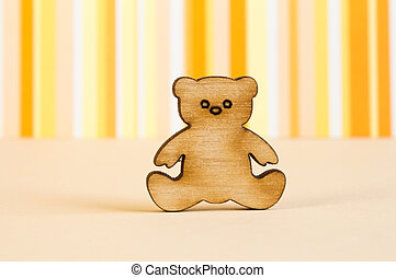 Wooden icon of Teddy bear on orange striped background