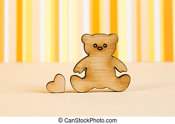 Wooden icon of Teddy bear with little heart on orange...