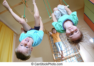 children hanging on gymnastic rings - three 5 year old...