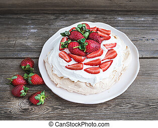 Rustic Pavlova cake with fresh strawberries and whipped...