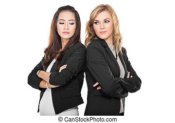 Two young businesswoman leaning againts each other, isolated