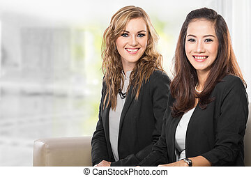 Two young businesswoman sitting next to each other, smile