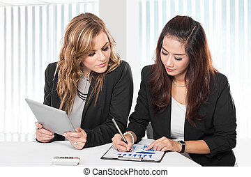 Two friendly businesswomen sitting and discussing new ideas...