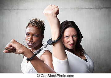 Angry women in handcuffs - Two angry women joind by a pair...