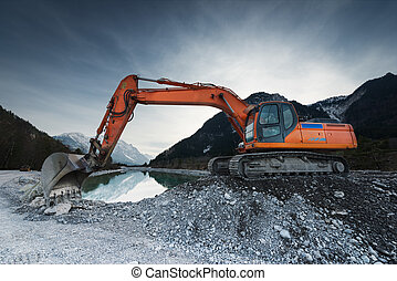 big shovel excavator standing on gravel stones before lake